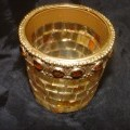 GLASS CANDLE HOLDER. DECORATED WITH SQUARE GOLD COLOURED PIECES OF GLASS IN A MOSAIC PATTERN, AND WITH IMITATION STONES ROUND THE RIM. THE HOLDER IS NOT SPECIFICALLY SHAPED OR DESIGNED TO HOLD...