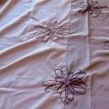 Tecido bordado, em peça, de cor bege, de valor inferior a € 17,50/kg, e com a seguinte composição têxtil: 52% Polyester e 48% algodão. O tecido apresenta aplicações de lantejoulas fixadas...