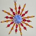 Dekorationsartikel in Nachbildung eines ca. 12,5 cm großen Kristalls. Das Erzeugnis besteht aus sternenförmig angeordneten Drähten aus unedlem Metall, auf denen verschiedenartige, meist orange-...