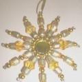 Ziergegenstand in Nachbildung eines ca. 11,5 cm großen Kristalls mit Aufhängevorrichtung. Das Erzeugnis besteht aus sternenförmig angeordneten Drähten aus unedlem Metall, auf denen orange-...