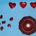 Zusammenstellung aus sechs Dekosteinen aus Kunststoff, einer Glasschale  (Glaswaren zur Verwendung bei Tisch) und drei Gelkerzen, sog. Valentinstag-Präsent, gemeinsam in einer Klarsichtpackung...