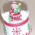 Ziergegenstand in Form einer Schneekugel, bestehend aus einem ca. 25 mm hohen, mit Schneekristall- und Tannenbaummotiven verzierten Standsockel (Durchmesser ca. 40 mm) und einer aufgesetzten,...
