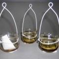 Glasware zur Innenausstattung, sog. Teelichthalter mit Draht, Art.-Nr.: 77758, 3er-Set im Pappkarton, siehe Foto,  - bauchiges, oben offenes Gefäß mit nach außen gebogenem Rand, - augenscheinlich...