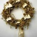 Es handelt sich um ein künstliches Gesteck in Form eines ca. 29 cm großen Kranzes aus Flechtstoffen, der u.a. mit goldfarbenen Disteln, Geschenkband, künstlichen Beeren und musizierenden Verkündigungsengeln...