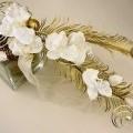 Es handelt sich um ein Weihnachtsgesteck aus Glas, Kunststoff, Eisendraht und Naturmaterialien in Form eines ca. 12,5 cm hohen, vasenartigen Erzeugnisses mit im Wesentlichen sechs goldfarbenen,...