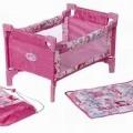 """Sog. """"Baby Born 2-in-1 Reisebett"""". Es handelt sich um ein faltbares, rechteckiges Reisebett für Puppen mit auf Metallrohren aufgezogenem, rosafarbenem Spinnstoff. Das Bett ist mit..."""