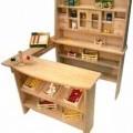 """Es handelt sich um ein ca. 80 x 90 x 114 cm großes Holzspielzeug sog. """"Kaufladen"""" aus naturfarbenem Holz. Es weist eine Verkaufstheke mit zwei Ablagefächern und einen Verkaufsständer..."""