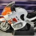 Es handelt sich um ein ca. 17 x 8 x 10 cm (L x B x H) großes, batteriebetriebenes, zweirädriges Motorrad aus Zinkguss und Kunststoff (charakterbestimmender Stoff nach dem äußeren Erscheinungsbild)....