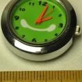 """Sog. """"analoges batteriebetriebenes Uhrwerk, im Wesentlichen bestehend aus einer runden Uhr in einem Metallgehäuse (Durchmesser: 2,6 cm, Höhe: 0,9 cm) aus einem grünfarbenen Ziffernblatt..."""