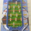 """Gesellschaftsspiel in Form eines sog. """"Kicker-Spiels"""", bestehend aus einem ca. 21 x 9 x 2 cm (L x B x H) großen, achteckigen Spielfeld aus Kunststoff mit einem grün gefärbten Spielfeldbelag..."""