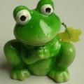 """Keramischer Ziergegenstand, sog. """"Dekofrosch mit Blume"""", Abbildung siehe Anlage,  - bemalte, lasierte, innen hohle Figur in Form eines sitzenden Frosches, - der Frosch kaut auf einer..."""