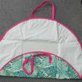 A CIRCULAR BEACH MAT/BAG. A BEACH MAT WITH ONE SIDE OF WOVEN PRINTED POLYESTER FABRIC THE OTHER OF POLURETHANE. HAS TWO WOVEN TEXTILE HANDLES TO CARRY AS A BAG WHEN FOLDED. CORNERS ARE FOLDED...